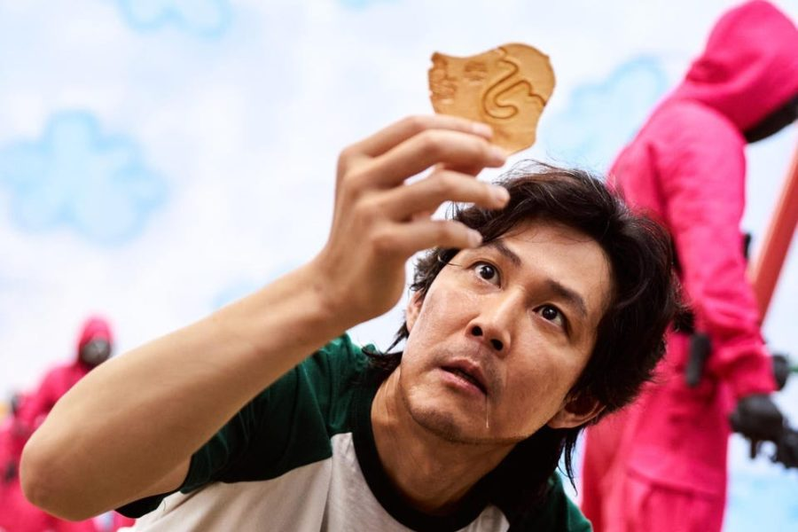 Seong Gi-hun, or player 456, holds up a dalgona candy as part of the Honeycomb Challenge.